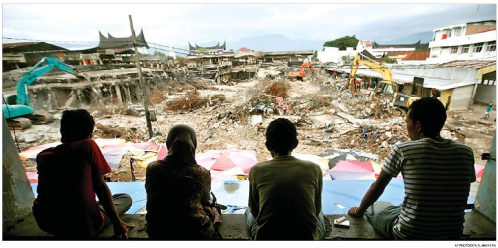 Warga menatap bangunan yang hancur tinggal puing-puing akibat gempa di Padang Sumatera Barat yang berkekuatan 7,6 skala richter